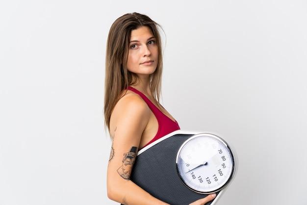 Jonge slowaakse vrouw geïsoleerd op wit met weegmachine