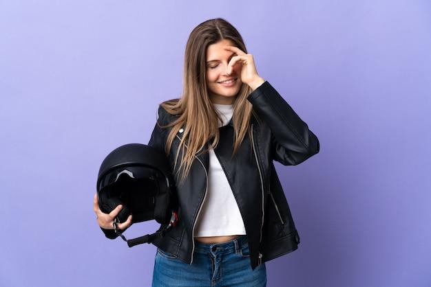 Jonge slowaakse vrouw met een motorhelm geïsoleerd op paarse achtergrond lachen