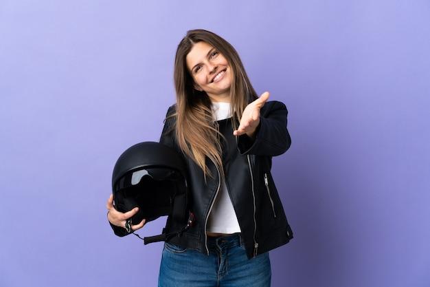 Jonge slowaakse vrouw met een motorhelm geïsoleerd op paarse muur handen schudden voor het sluiten van een goede deal
