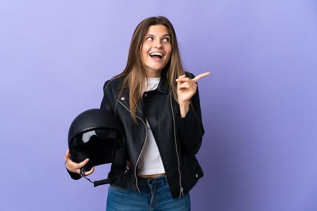 Jonge slowaakse vrouw met een motorhelm geïsoleerd op paarse muur met de bedoeling de oplossing te realiseren terwijl ze een vinger opheft