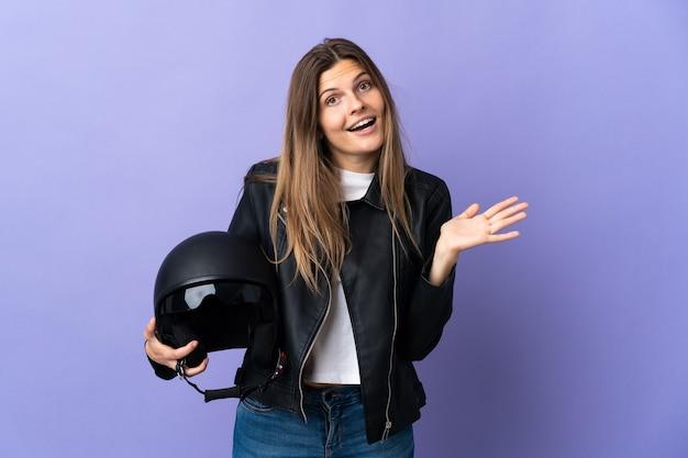 Jonge slowaakse vrouw met een motorhelm geïsoleerd op paarse muur met geschokte gelaatsuitdrukking
