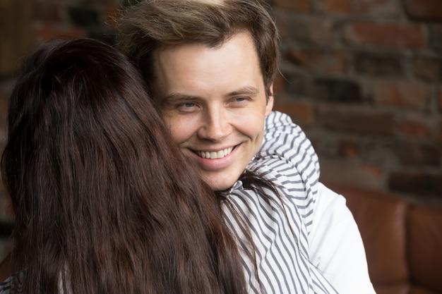 Jonge sluwe leugenaarmens die gelukkig glimlachen terwijl vrouw hem omhelst