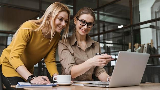 Jonge smileyonderneemsters die met laptop bij bureau werken