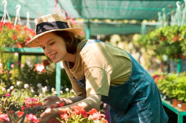 Jonge smileyvrouw die in een serre werkt