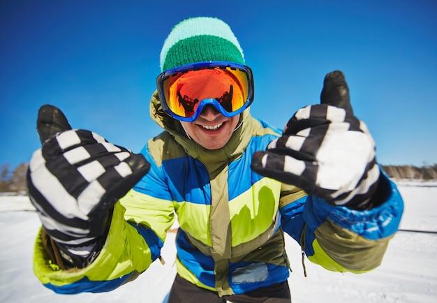 Jonge snowboarder die pret in de sneeuw