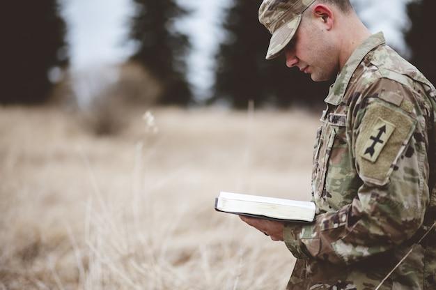 Jonge soldaat die een bijbel leest in een veld