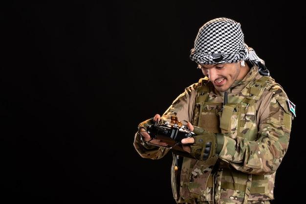 Jonge soldaat in camouflage met afstandsbediening op zwarte muur