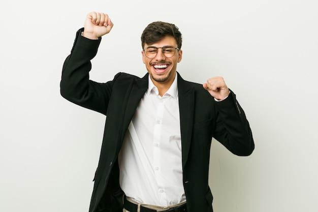 Jonge spaanse bedrijfsmens die een speciale dag viert, springt en heft wapens met energie op.