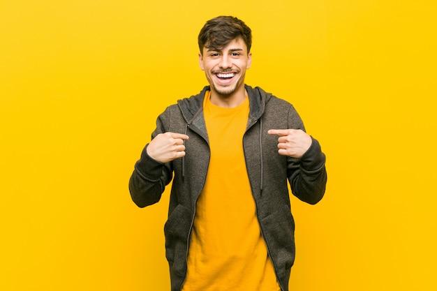 Jonge spaanse casual man verrast wijzend met vinger, breed glimlachend.