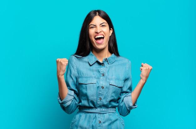 Jonge spaanse casual vrouw agressief schreeuwen met een boze uitdrukking of met gebalde vuisten het vieren van succes