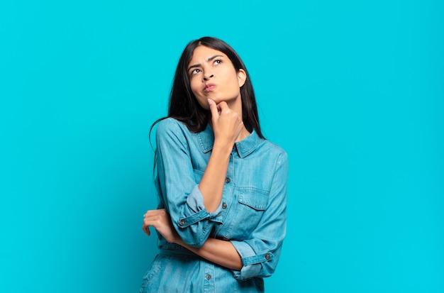 Jonge spaanse casual vrouw denken, twijfelachtig en verward voelen, met verschillende opties, zich afvragend welke beslissing ze moeten nemen