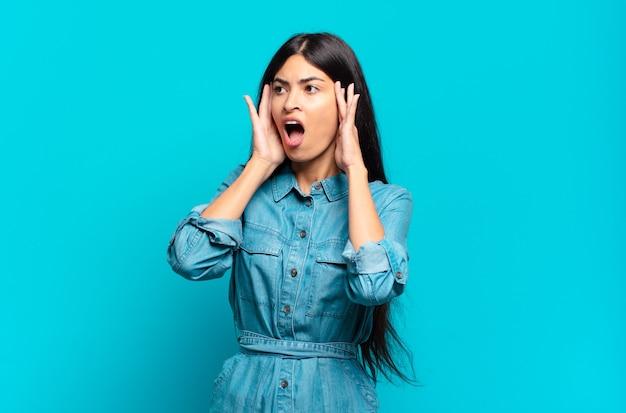 Jonge spaanse casual vrouw die blij, opgewonden en verrast voelt, naar de zijkant kijkend met beide handen op het gezicht