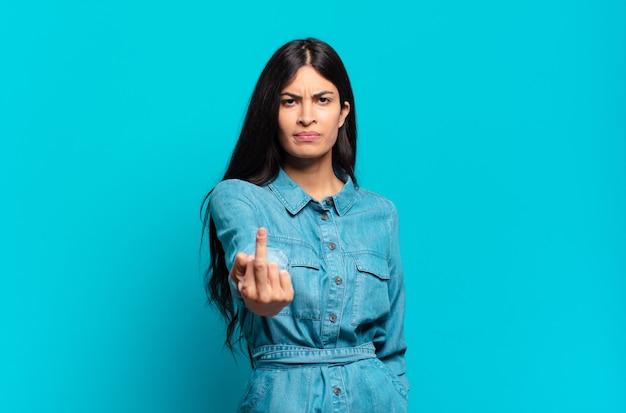 Jonge spaanse casual vrouw die zich boos, geïrriteerd, opstandig en agressief voelt, de middelvinger omdraait, terugvecht