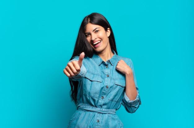 Jonge spaanse casual vrouw die zich trots, zorgeloos, zelfverzekerd en gelukkig voelt, positief glimlacht met omhoog duimen