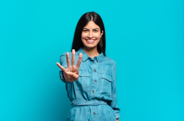 Jonge spaanse casual vrouw glimlacht en ziet er vriendelijk uit, nummer vier of vierde met hand naar voren, aftellend