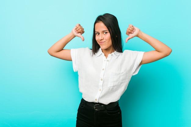 Jonge spaanse coole vrouw tegen een blauwe muur voelt zich trots en zelfverzekerd, bijvoorbeeld om te volgen.