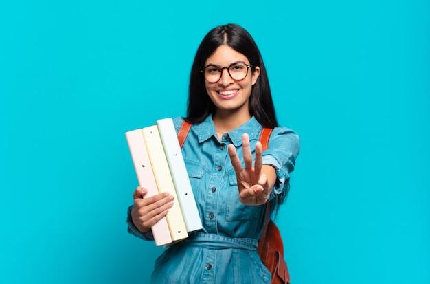 Jonge spaanse en studentenvrouw die vriendelijk glimlacht kijkt, nummer drie of derde met vooruit hand toont, aftellend