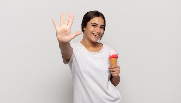 Jonge spaanse en vrouw die vriendelijk glimlacht kijkt, nummer vijf of vijfde met vooruit hand toont, aftellend