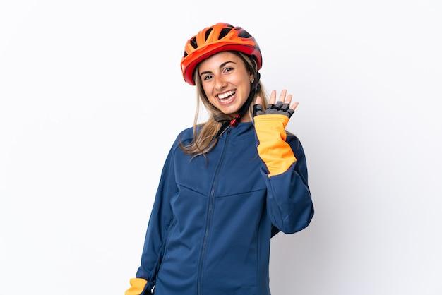 Jonge spaanse fietservrouw die op witte muur wordt geïsoleerd die met hand met gelukkige uitdrukking groeten