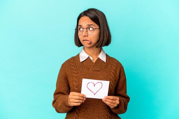 Jonge spaanse gemengd ras vrouw met een hart papier verward, voelt twijfelachtig en onzeker.