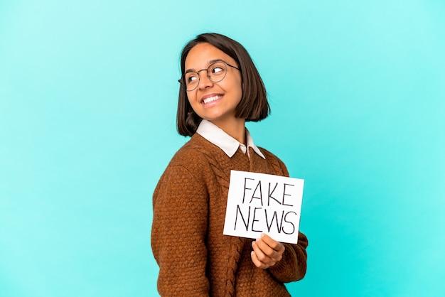 Jonge spaanse gemengd ras vrouw met een plakkaat nep nieuws kijkt opzij glimlachend, vrolijk en aangenaam.