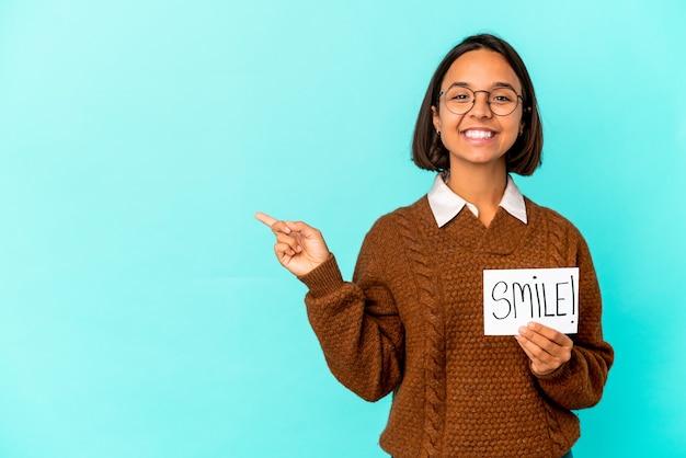 Jonge spaanse gemengde rasvrouw die een glimlachnota houdt die opzij glimlacht en wijst, iets op lege ruimte toont.