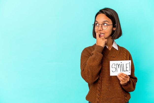 Jonge spaanse gemengde rasvrouw die een glimlachnota houdt ontspannen na te denken over iets dat naar een exemplaarruimte kijkt.