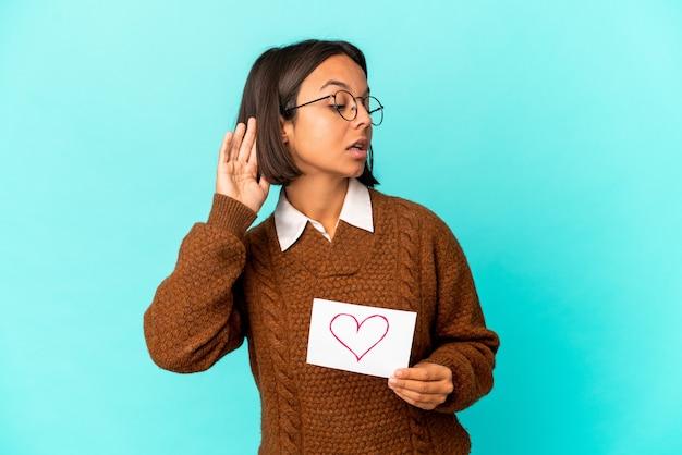 Jonge spaanse gemengde rasvrouw die een hartdocument houden dat een roddel probeert te luisteren.