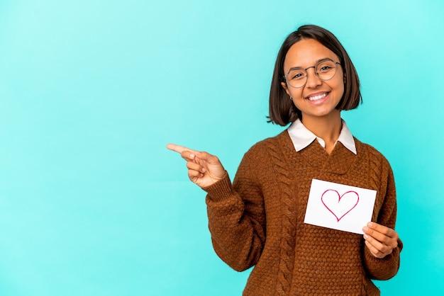 Jonge spaanse gemengde rasvrouw die een hartdocument houden dat en opzij glimlacht richt, iets op lege ruimte toont.
