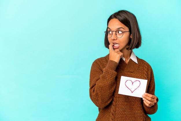 Jonge spaanse gemengde rasvrouw die een hartdocument houden ontspannen denkend aan iets dat een exemplaarruimte bekijkt.