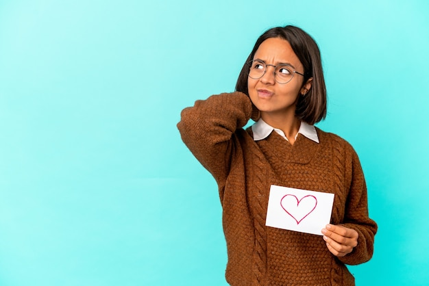 Jonge spaanse gemengde rasvrouw die een hartdocument houdt dat achterkant van het hoofd raakt, denkt en een keus maakt.