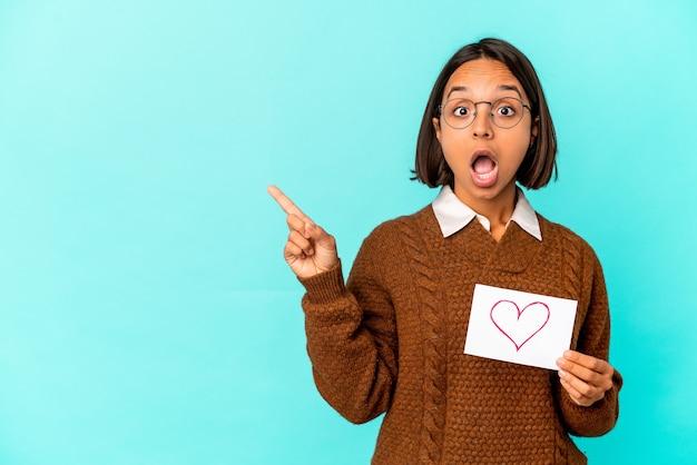 Jonge spaanse gemengde rasvrouw die een hartdocument houdt dat naar de kant wijst