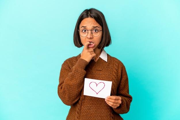 Jonge spaanse gemengde rasvrouw die een hartdocument houdt dat vingernagels bijt, zenuwachtig en zeer bezorgd.