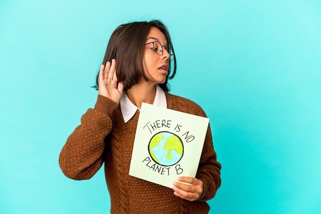 Jonge spaanse gemengde rasvrouw die een planeet houdt sparen aanplakbiljet dat probeert een roddel te luisteren.
