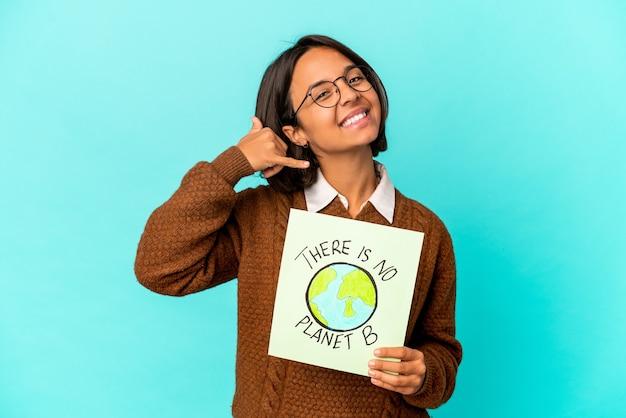 Jonge spaanse gemengde rasvrouw die een planeet sparen aanplakbiljet houden dat een mobiel telefoongesprekgebaar met vingers toont.