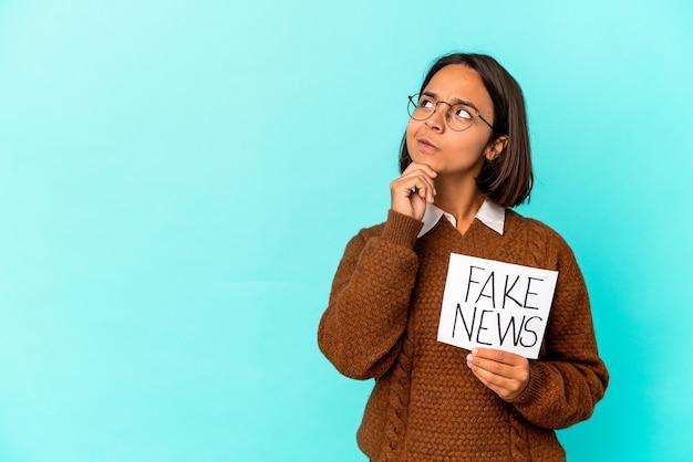 Jonge spaanse gemengde rasvrouw die een vals nieuwsaanplakbiljet houdt dat zijwaarts kijkt met twijfelachtige en sceptische uitdrukking.