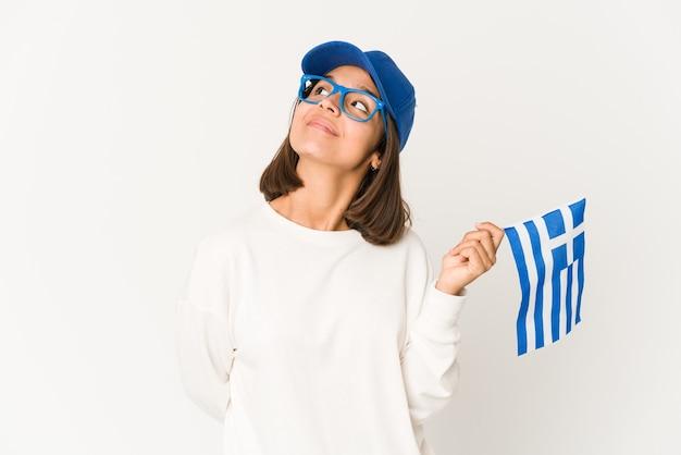 Jonge spaanse gemengde rasvrouw die een vlag van griekenland houden die van het bereiken van doelstellingen droomt