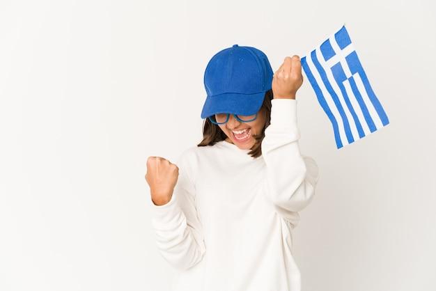 Jonge spaanse gemengde rasvrouw die een vlag van griekenland houden die vuist opheft na een overwinning, winnaarconcept.