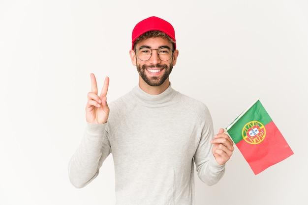 Jonge spaanse gemengde rasvrouw die een vlag van portugal houden die nummer twee met vingers toont.