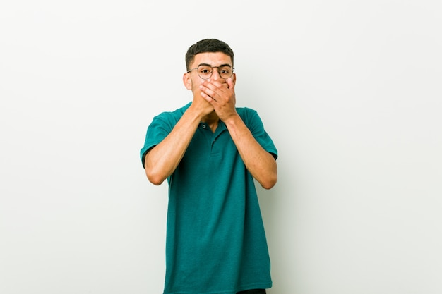 Jonge spaanse geschokte mens het behandelen van mond met handen.