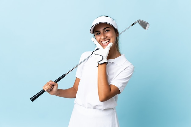 Jonge spaanse golfer vrouw over geïsoleerde blauwe muur blij en lachend