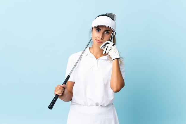 Jonge spaanse golfspelervrouw isoleerde blauwe muur die een idee denkt