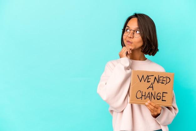 Jonge spaanse halfbloedvrouw die een inspirerende veranderingsboodschap op karton houdt die opzij kijkt met een twijfelachtige en sceptische uitdrukking.