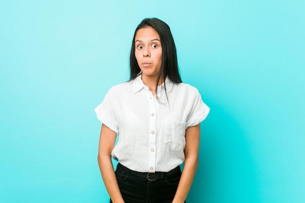 Jonge spaanse koele vrouw tegen een blauwe muur haalt schouders op en verwarde open ogen.