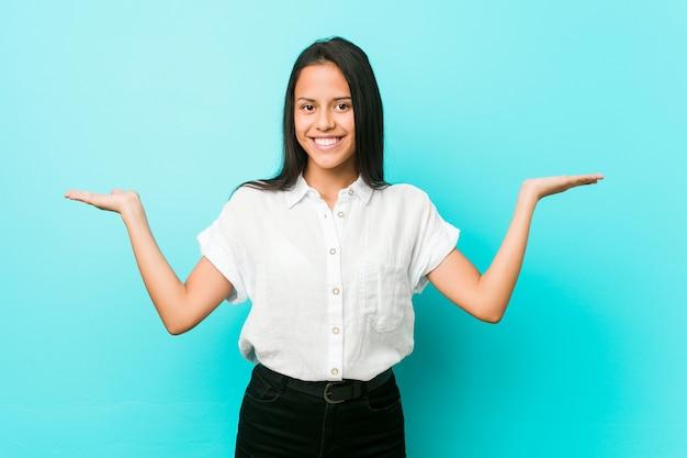 Jonge spaanse koele vrouw tegen een blauwe muur maakt schaal met armen, voelt zich gelukkig en zelfverzekerd.