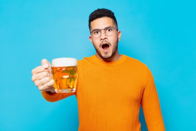 Jonge spaanse man bang uitdrukking en met een biertje