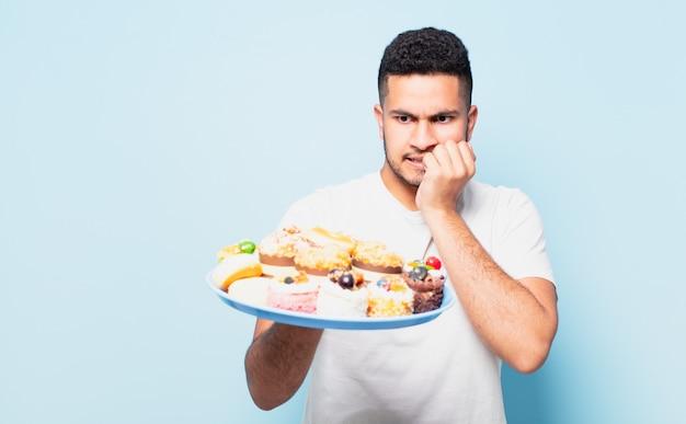 Jonge spaanse man bang uitdrukking met cupcakes