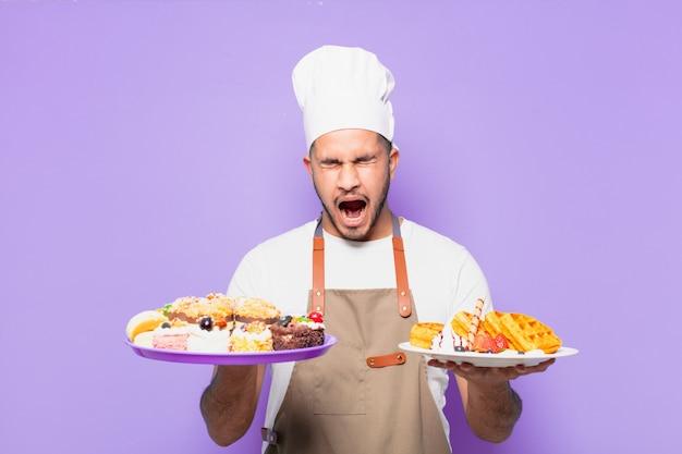 Jonge spaanse man boze uitdrukking. chef-kok met wafels concept
