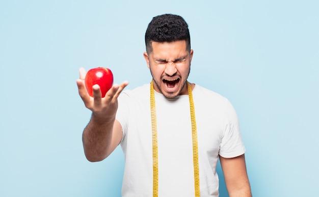 Jonge spaanse man boze uitdrukking en een appel te houden. dieet concept