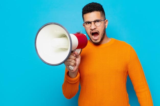 Jonge spaanse man boze uitdrukking en met een megafoon